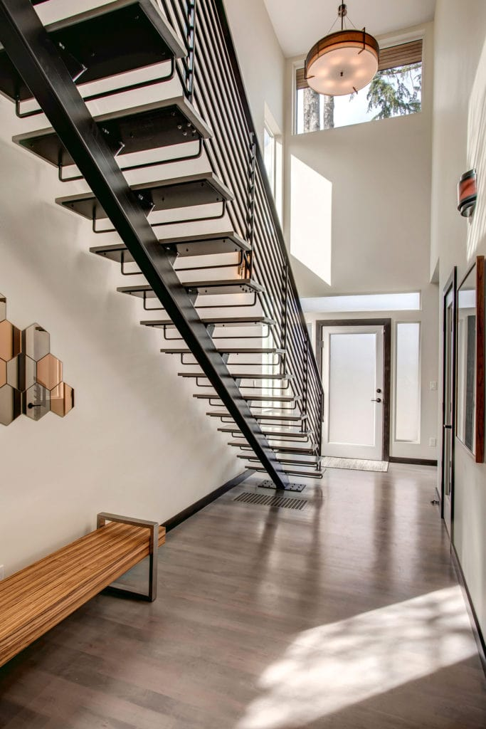 Architecturally dramatic steel staircase showcases the two story entryway.